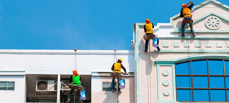 Workers Painting a Tall Commercial Building